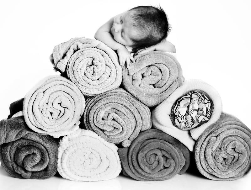 Baby and blankets. Baby asleep on top of a pyramid made with blankets royalty free stock photography