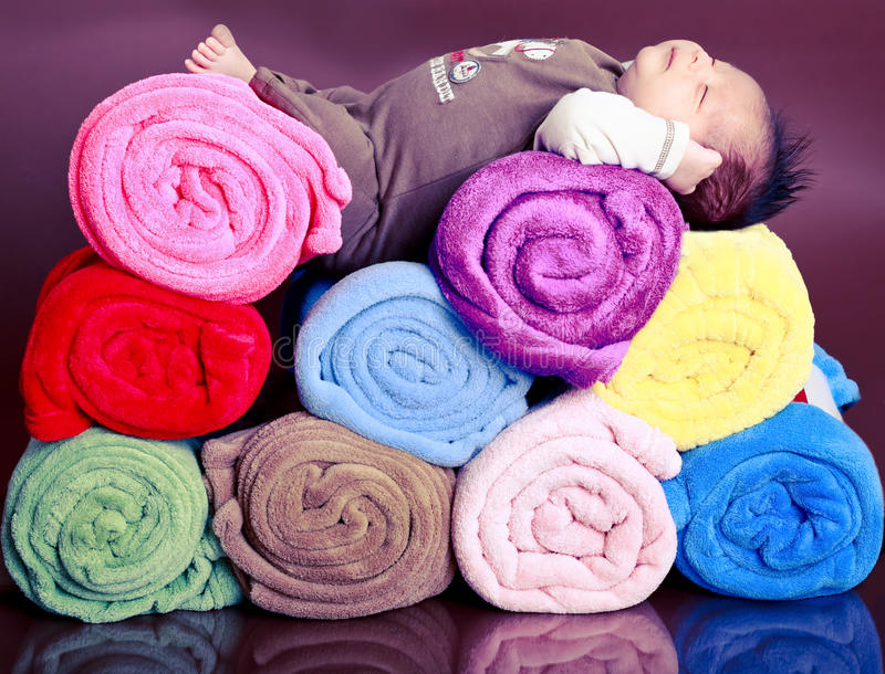 Baby and blankets. Baby asleep on top of bunch of rolled up blankets stock image