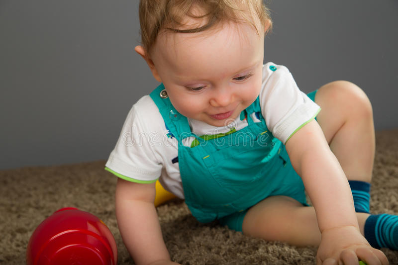 Baby in a blue bib pants stock image