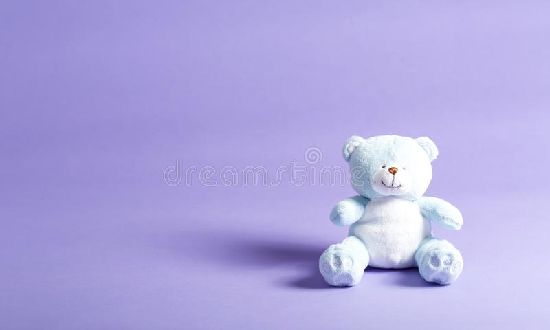 Baby blue child`s teddy bear on a purple background royalty free stock photography