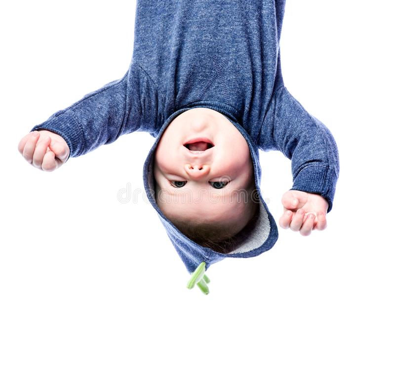 Baby in blue hoodie upside down. Cheerful boy with blue eyes stock photo