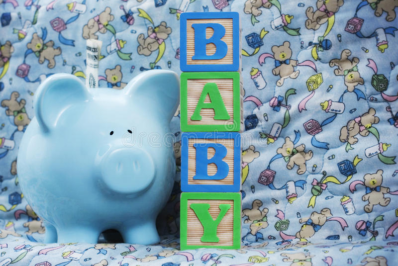 Baby with Blue Piggy Bank. Wooden blocks spell Baby next to a blue piggy bank over a baby blanket royalty free stock photos
