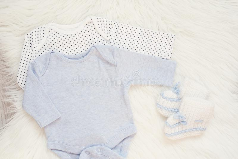 Baby Bodysuit Mockup. Styled Stock Photography. Clothes For A Boy. Jumpsuits, Rompers On A White Fur Carpet. Newborn Baby Concept. Baby Boy Clothes Set royalty free stock photos
