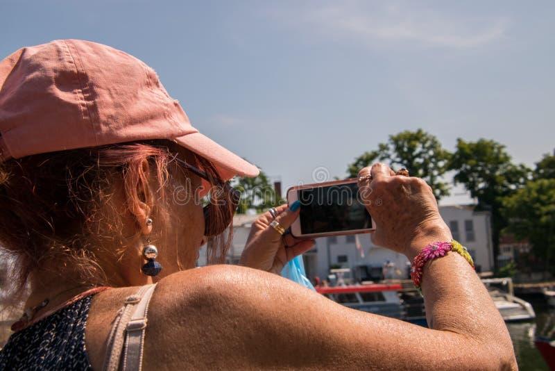 Baby boomer de femme utilisant la casquette de baseball rose prenant la photo d'a images stock