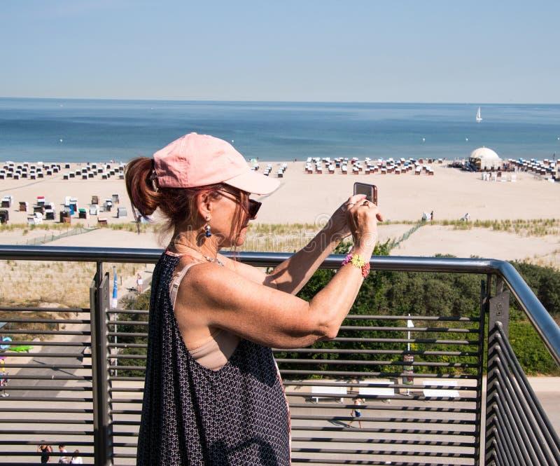 Baby boomer de femme utilisant la casquette de baseball rose sur la terrasse prenant pi photos libres de droits