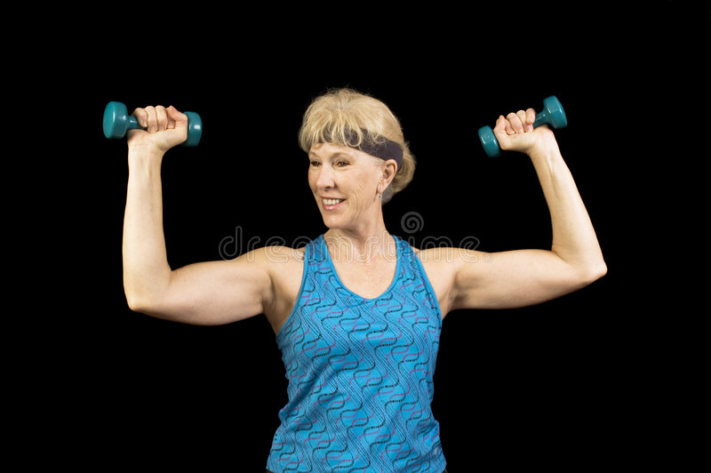 Baby-boomer female exercising. Middle-aged, baby-boomer woman exercising with weights and enjoying it royalty free stock photo