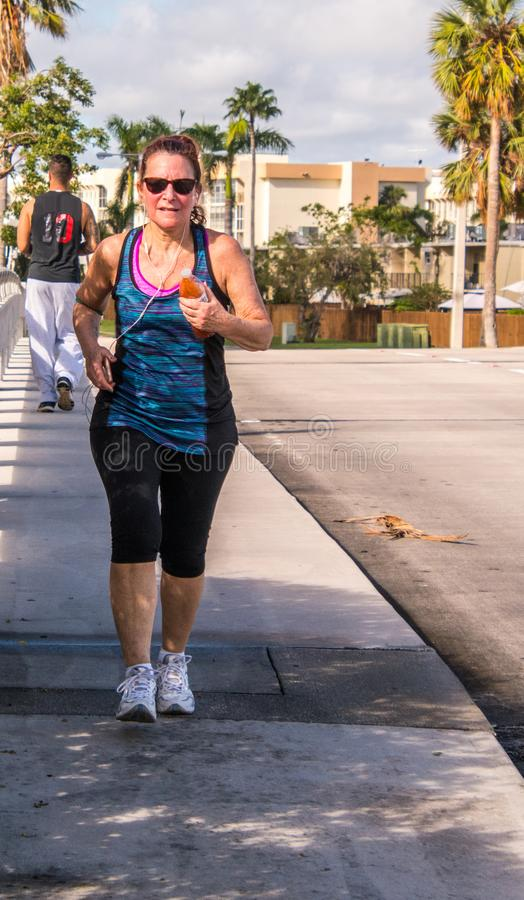 Baby boomer woman exercising. Baby boomer woman power walking for exercise wearing gym clothes on a sidewalk with palm trees in background stock photo