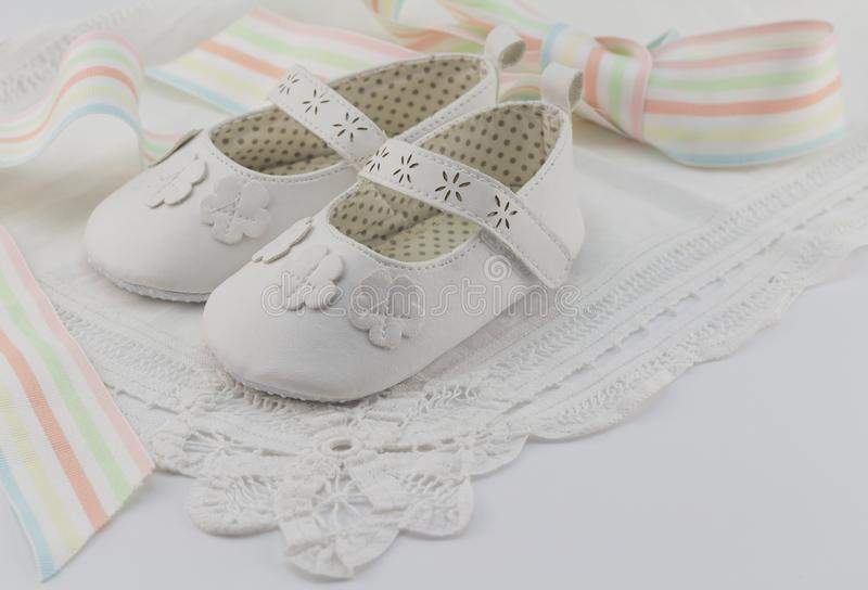 Baby booties background with white lace and pastel colour ribbon royalty free stock photo