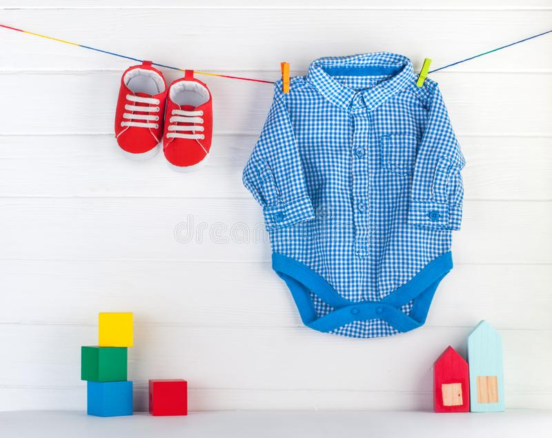 Baby booties and blue bodykit on clothespins and wooden toys over white background royalty free stock photos