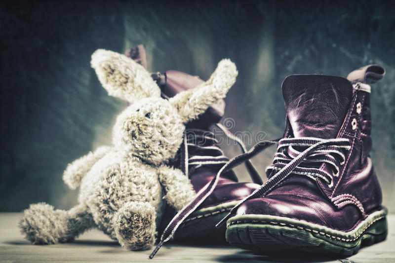 Baby boots and plush rabbit toy close up shot. Grungy backgrounds royalty free stock images