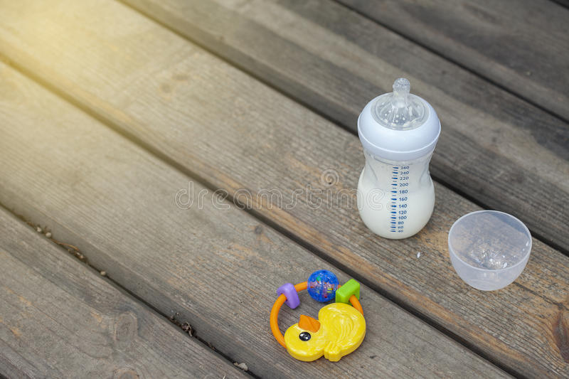 Baby: bottle and toy. On a wooden background on a walk royalty free stock image
