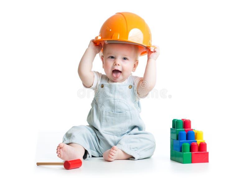 Baby in bouwvakker het spelen speelgoed op een witte achtergrond wordt geïsoleerd die royalty-vrije stock foto