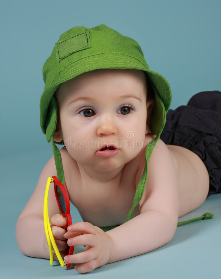 Baby boy. Adorable 8 months cacasian baby boy playing with sunglasses stock photo