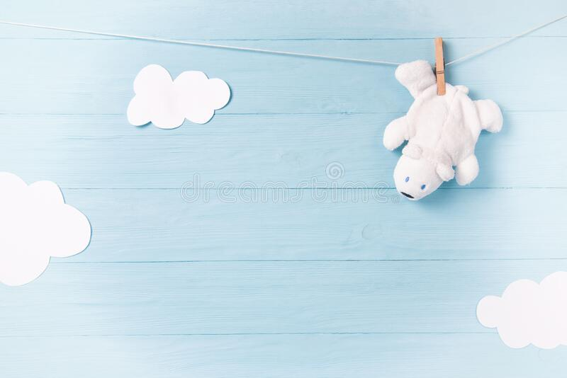 Baby boy background with white teddy bear toy on a clothesline and clouds. Baby boy newborn background with white teddy bear toy on a clothesline and clouds royalty free stock photography