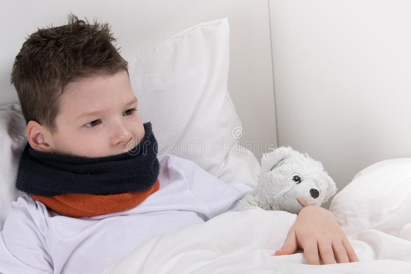 Baby boy in bed, with a sore throat, recovers stock photography