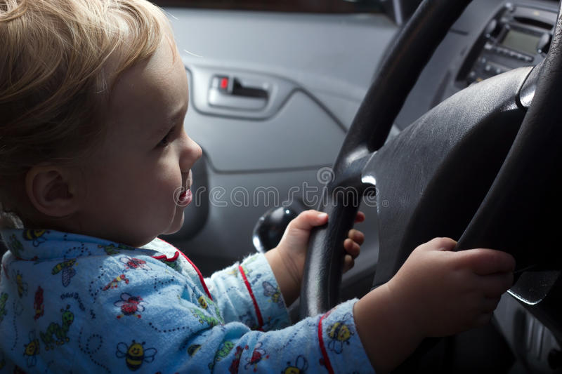 Baby boy behind the steering wheel royalty free stock photo