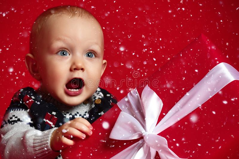 Baby boy with big blue eyes wearing warm sweater sitting in front of his present in wrapped box with ribbon over red background. royalty free stock photography