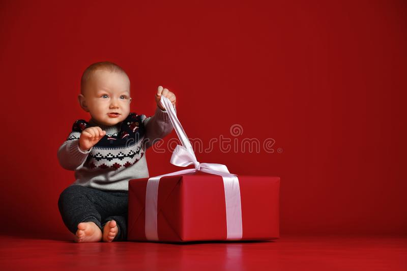 Baby boy with big blue eyes wearing warm sweater sitting in front of his present in wrapped box with ribbon over red background stock image