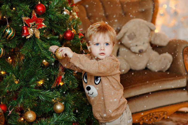 Baby boy blonde in beige sweater dresses up Christmas tree, hang stock image