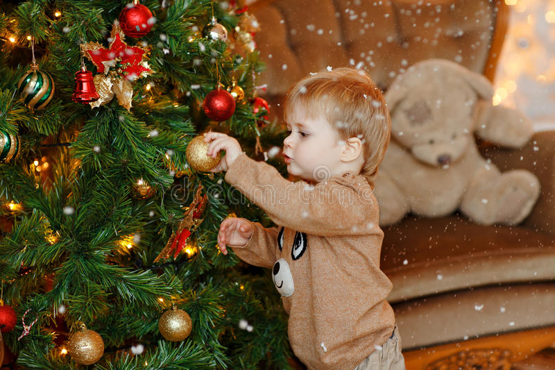 Baby boy blonde in beige sweater dresses up Christmas tree, hang royalty free stock photos