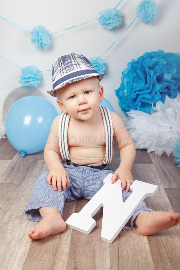 Baby boy with blue eyes barefoot in pants with suspenders and hat, sitting on wooden floor in studio, holding large letter N. Portrait of cute adorable Caucasian stock image