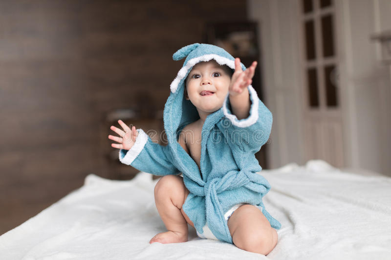 Baby boy in blue robe. Happy baby boy in blue robe posing on bed stock images