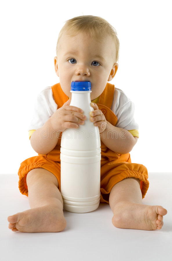 Baby boy with bottle. Little baby boy sitting on the floor. Holding and biting a bottle of milk. Looking at camera, whole body. Front view royalty free stock image