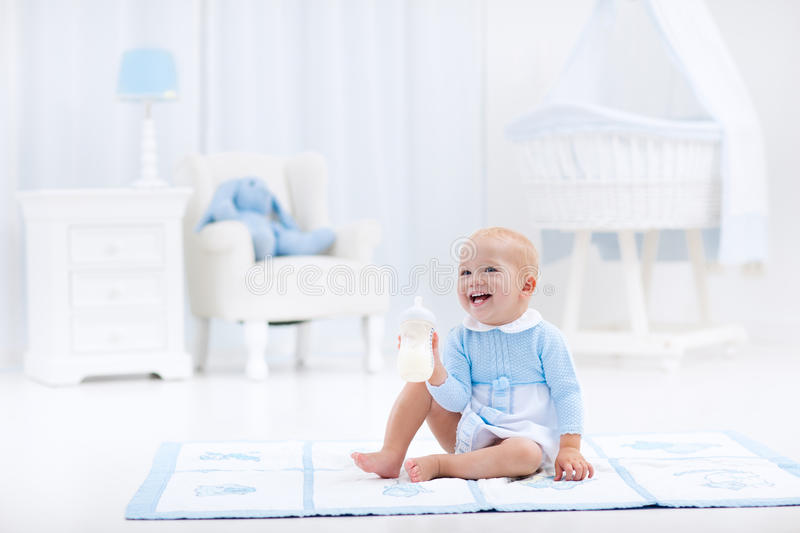 Baby boy with bottle drinking milk or formula. Adorable baby boy playing on a blue floor mat and drinking milk from a bottle in a white sunny nursery with stock image