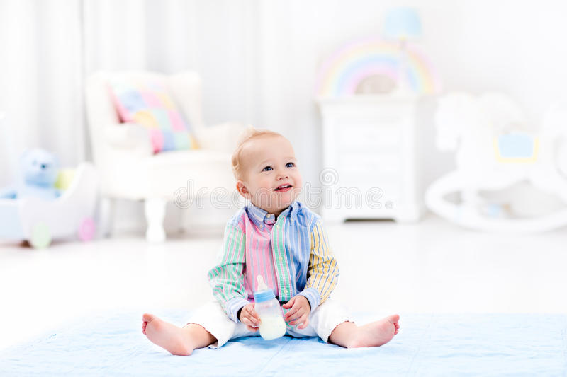 Baby boy with bottle drinking milk or formula. Adorable baby boy playing on a blue floor mat and drinking milk from a bottle in a white sunny nursery with royalty free stock images