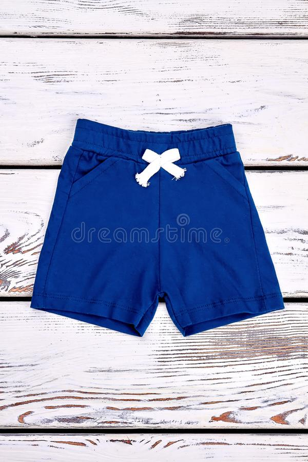 Baby boy casual summer shorts. Toddler boy natural cotton shorts on vintage wooden background, top view. Kids summer apparel on sale stock photos