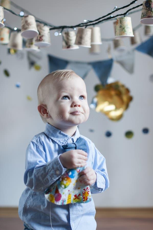 Baby boy celebrating his birthday. Surprised baby boy celebrating his birthday royalty free stock image