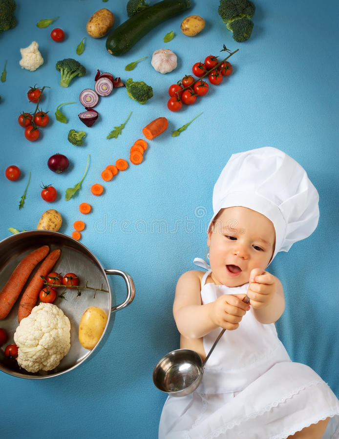 Baby boy in chef hat with cooking pan. And raw vegetables stock image