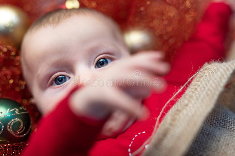 Baby boy among Christmas decorations. Blue-eyed baby boy in red pajamas laying among Christmas decorations shot from above in close-up stock photos