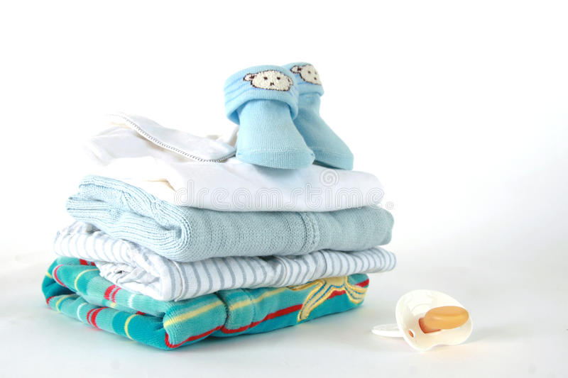 Baby boy clothes. Stack of baby clothes in blue with white pacifier royalty free stock images