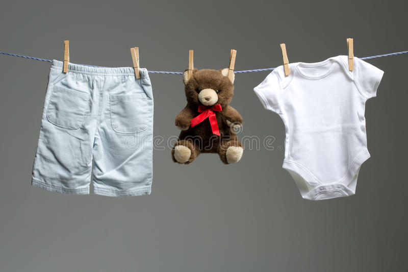 Baby boy clothes, a teddy bear on the clothesline stock images