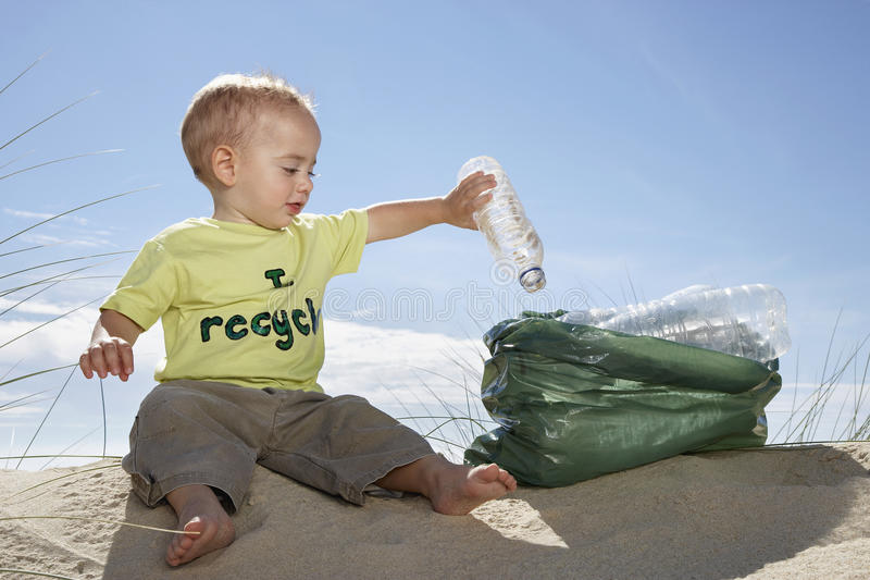 Baby Boy Collecting Bottle In Plastic Bag On Beach royalty free stock photo