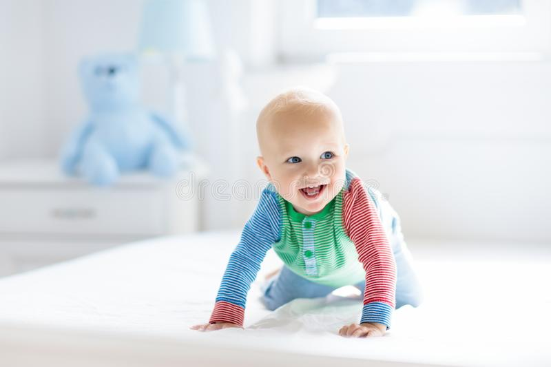 Baby boy crawling on bed. Little child playing in white sunny bedroom. Infant kid learning to crawl. Nursery for children. Textile, clothing and bedding for stock images