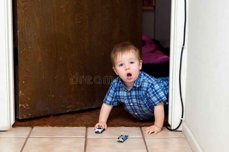 Baby Boy Crawls Through Doorway With A Police Car and an Overturned Blue Car royalty free stock photos