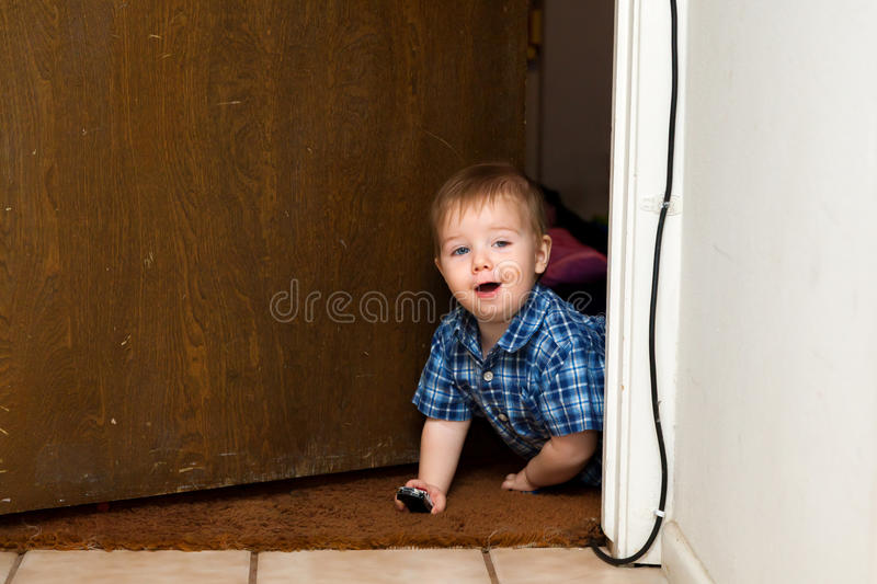 Baby Boy Crawls Through Doorway with a Smile. A baby boy crawls through a doorway with a smile and two toy cars in his hands stock photos