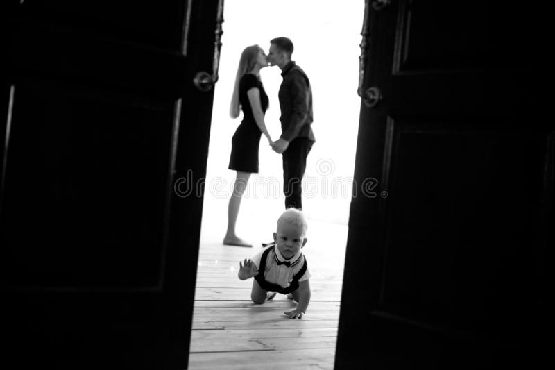 Baby boy crawls at the floor on background of his kissing parents royalty free stock photo