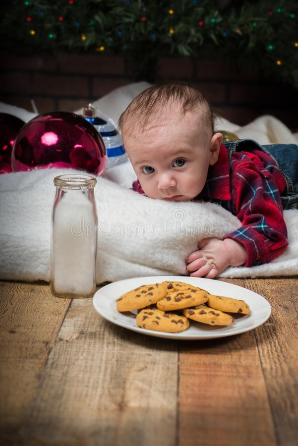 Baby laying under tree and reaching Christmas cookies. Baby boy dressed in flannel laying under a Christmas tree reaching for cookies stock photos