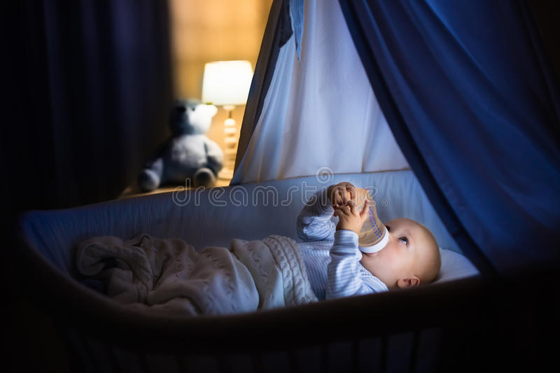 Baby boy drinking milk in bed royalty free stock images