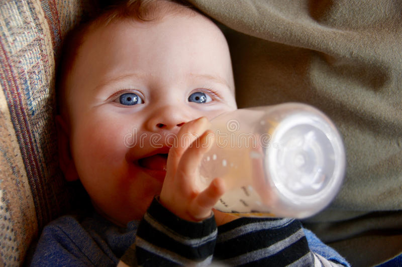 Baby boy drinking milk from a bottle and smiling. Blue-eyed baby boy is drinking milk from a bottle with a smile on his face royalty free stock images