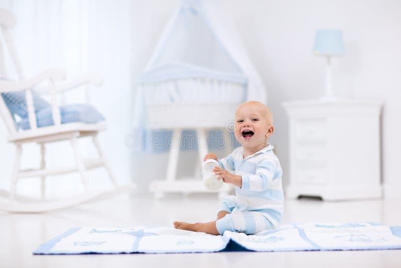 Baby boy drinking milk in sunny nursery royalty free stock photo