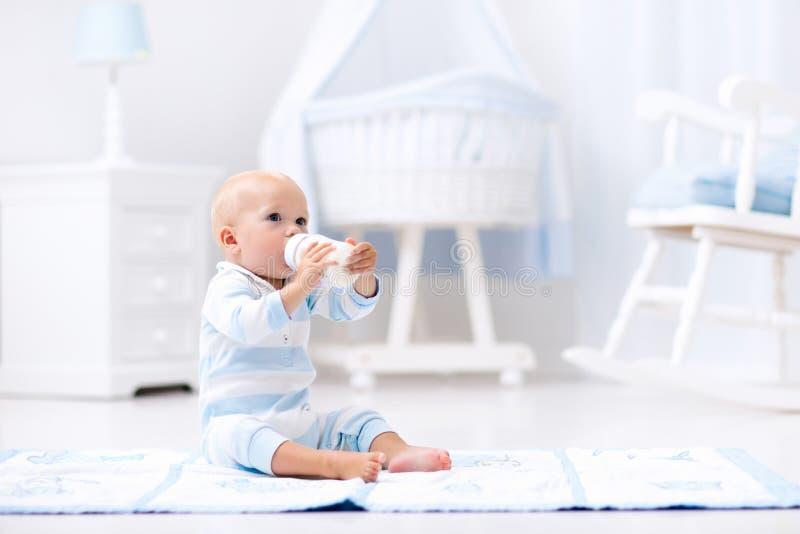 Baby boy drinking milk in sunny nursery stock photos
