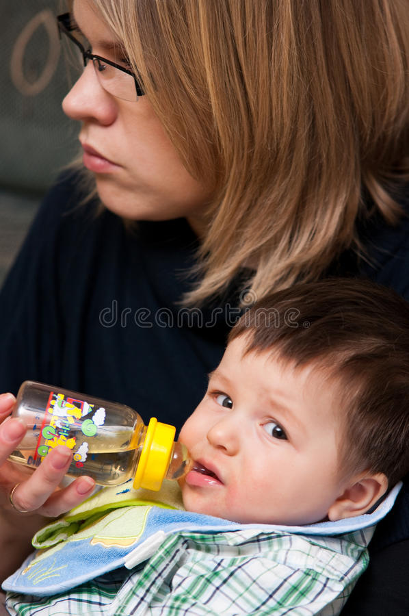 Baby boy drinks from bottle stock photography