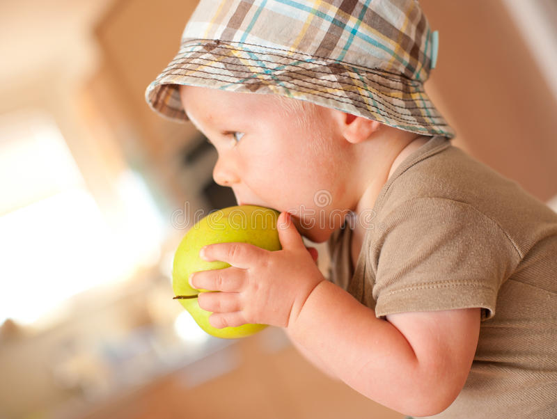 Baby boy eating apple. Baby boy eating fresh green apple with smile on his face royalty free stock image