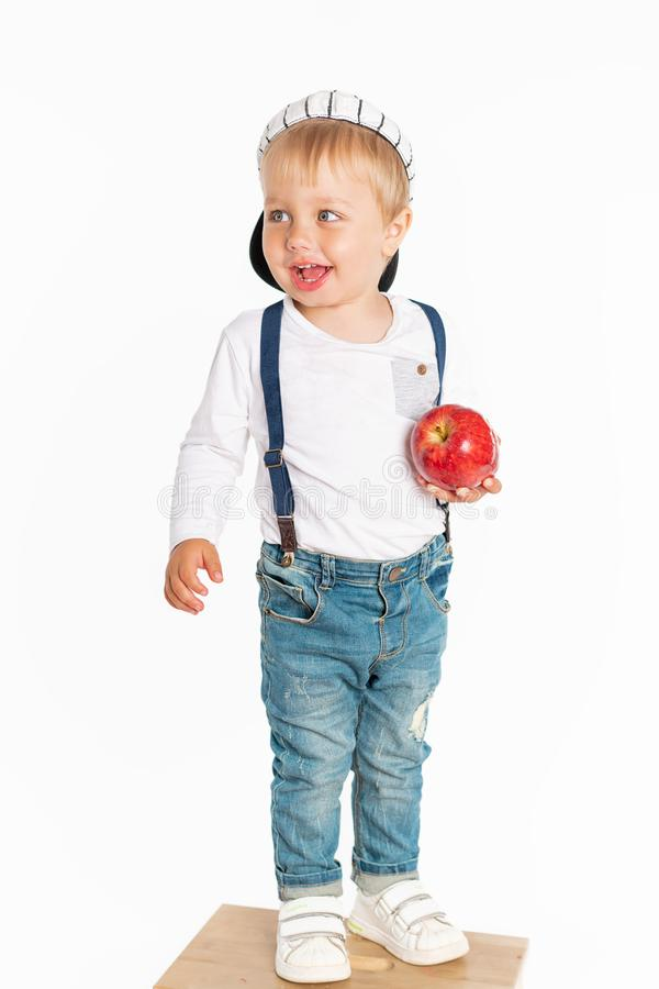 Baby boy eating apple and smiling in the studio isolated on white background stock photo
