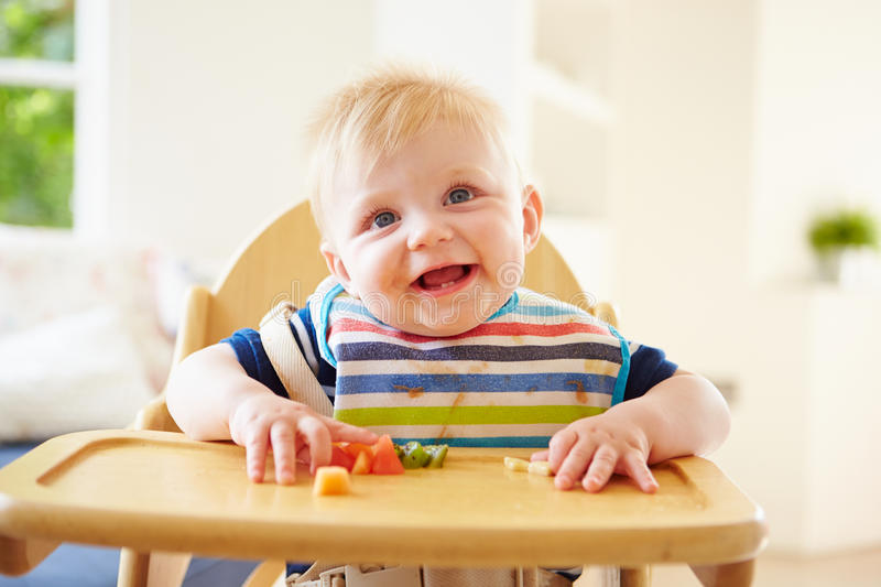 Baby Boy Eating Fruit In High Chair royalty free stock image