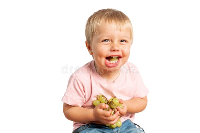 Baby boy eating grapes and smiling in the studio isolated on white background. Concept healthy food royalty free stock image